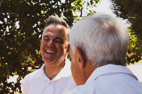 An elderly father and adult son laughing and talking together